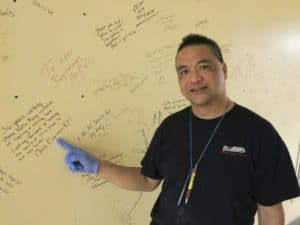 Rowell Bulson, a mover, shows some of the sentiments scribbled by St Joe's employees on a wall in the old hospital building. Bulson is one of an army of workers helping with the decommissioning of the 141-year-old hospital